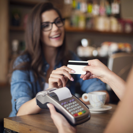 Photo pour Happy woman paying for cafe by credit card  - image libre de droit