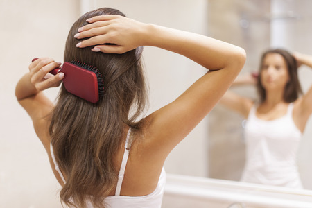 Photo for Young woman brushing healthy hair in front of a mirror  - Royalty Free Image