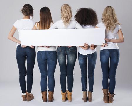 Foto de Girls in jeans holding empty banner - Imagen libre de derechos