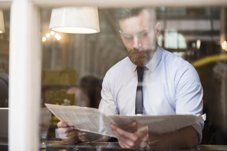 Photo for Young businessman reading newspaper - Royalty Free Image