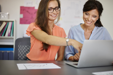 Foto de Two women working on computer in the office - Imagen libre de derechos