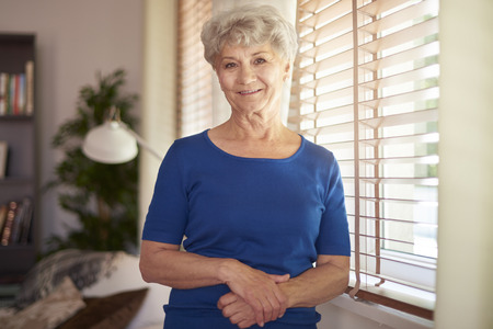 Photo for Cheerful grandmother standing next to the window - Royalty Free Image