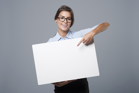 Photo for Beautiful businesswoman showing on empty whiteboard - Royalty Free Image