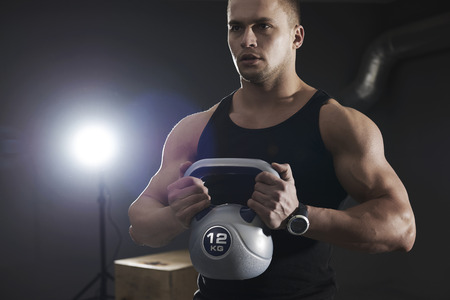 Photo for Well built man lifting kettlebell - Royalty Free Image