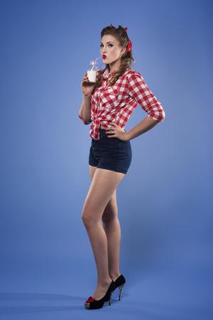 Photo pour Pin up girl drinking milk - image libre de droit