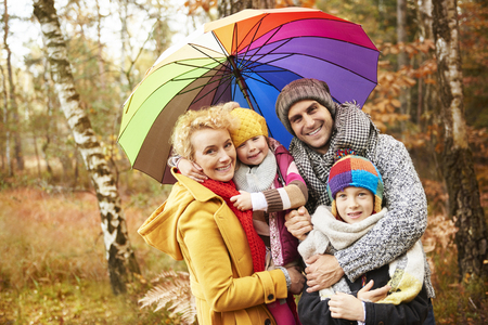 Photo for Family looking for shelter with umbrella - Royalty Free Image