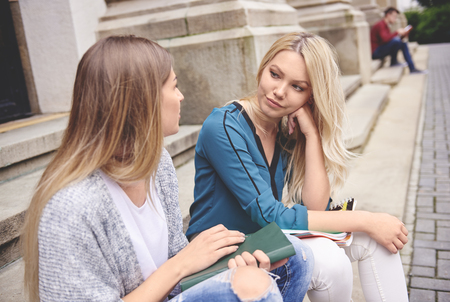 Photo for Two female students sitting and talking - Royalty Free Image