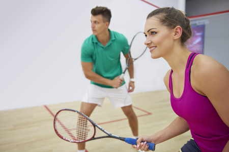 Foto de Focused man and woman playing squash together - Imagen libre de derechos