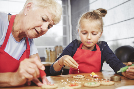 Foto de Grandma with girl applying icing on cookies - Imagen libre de derechos