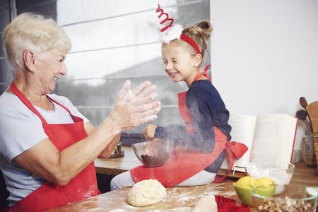 Foto de Grandmother and granddaughter enjoying in kitchen - Imagen libre de derechos