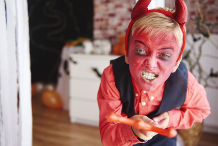 Photo for Boy in devil costume trying to scare people - Royalty Free Image