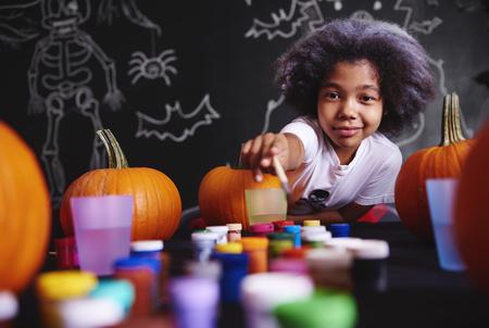 Photo pour Girl reaching for watercolor paints - image libre de droit