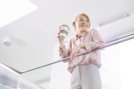 Photo for Cheerful businesswoman with mug of coffee leaning on a railing - Royalty Free Image
