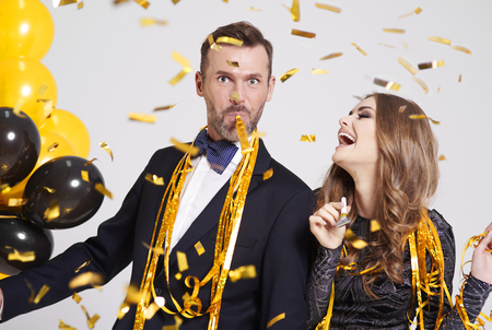 Photo pour Couple with horn blower partying  - image libre de droit