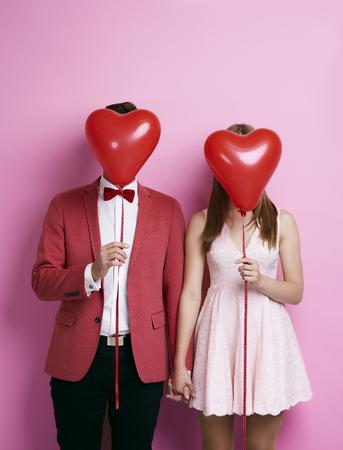 Photo pour Unrecognizable couple with balloon holding hands  - image libre de droit
