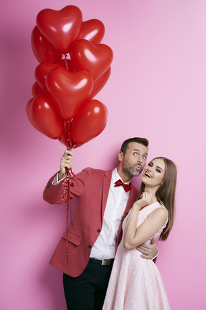 Foto de Affectionate couple with heart shape balloons flirting  - Imagen libre de derechos