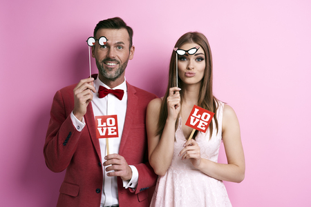 Photo for Portrait of couple with photo booth partying   - Royalty Free Image