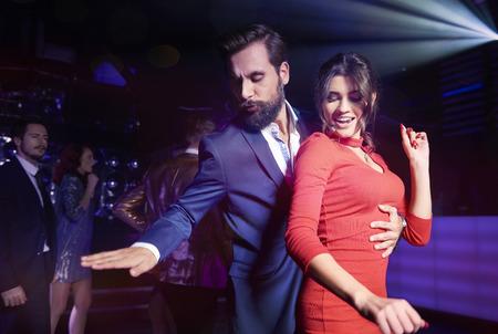 Photo pour Embraced couple dancing at night club  - image libre de droit