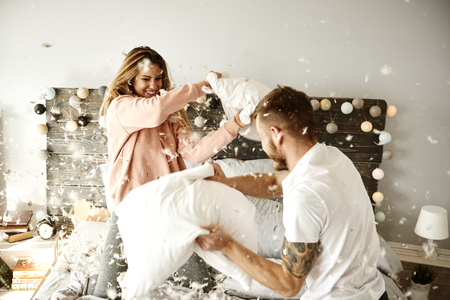 Photo pour Couple having a fun while pillow fight - image libre de droit
