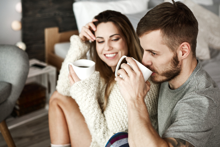 Photo pour Cheerful man and woman drinking coffee in bedroom  - image libre de droit