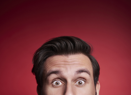Photo for Part of terrified man peeking at studio shot  - Royalty Free Image