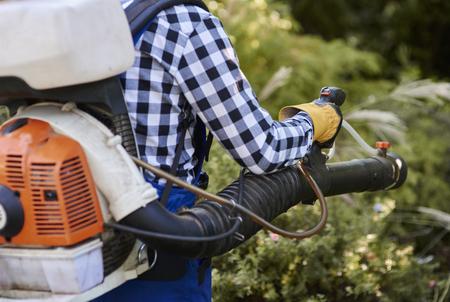 Photo pour Man using modern leaf blower  - image libre de droit