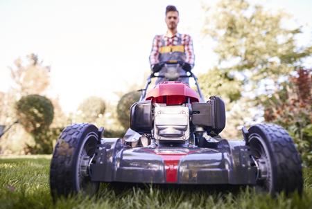 Foto de Defocused gardener pushing modern mower   - Imagen libre de derechos