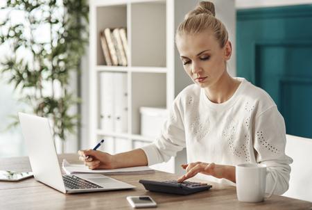 Foto de Concentrated woman budgeting at office  - Imagen libre de derechos