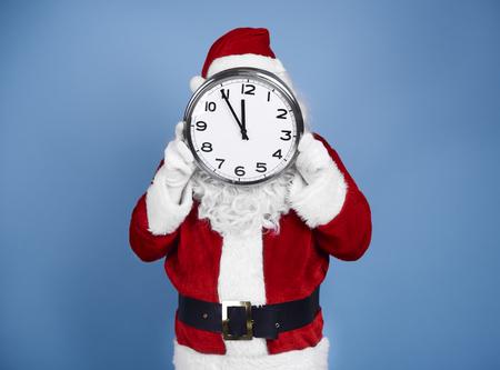 Photo pour Santa Claus holding clock in front of his face - image libre de droit
