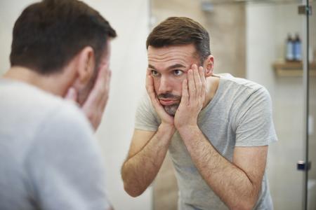 Foto de Worried man looking in the mirror in bathroom - Imagen libre de derechos