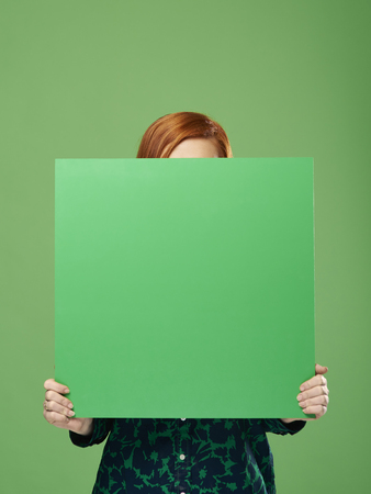 Photo pour Young woman holding banner with copy space in studio shot - image libre de droit