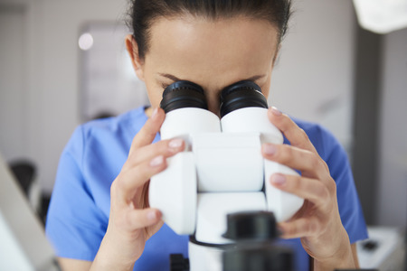 Foto de Focused dentist looking through the microscope  - Imagen libre de derechos