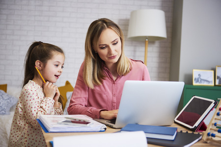 Foto de Young mother working from home with daughter - Imagen libre de derechos
