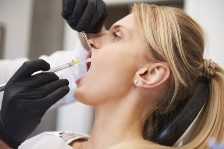 Foto de Stomatologist giving woman anesthesia in dentist's clinic  - Imagen libre de derechos