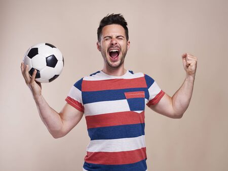 Foto de Ecstatic male fan with soccer ball cheering - Imagen libre de derechos