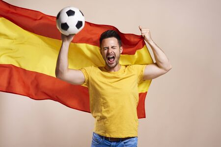 Foto de Screaming Spanish fan holding flag and soccer ball - Imagen libre de derechos