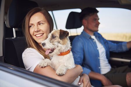 Photo pour Young couple and their dog traveling together in a car - image libre de droit