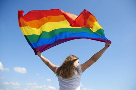 Foto de Rear view of young woman waving rainbow flag - Imagen libre de derechos