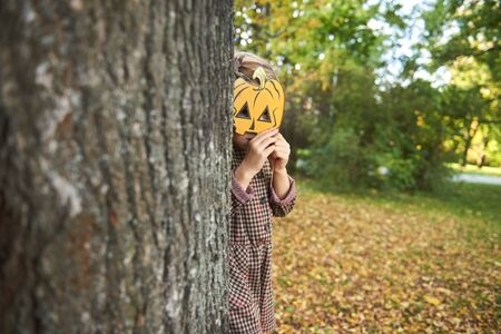 Photo for Little girl holding halloween pumpkin in front of his face - Royalty Free Image