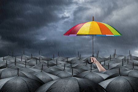 Photo for rainbow umbrella in mass of black umbrellas - Royalty Free Image