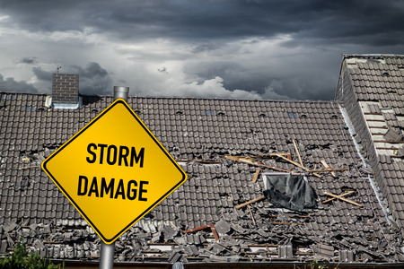 Photo for yellow damage warning sign in front of roof of house damaged by heavy hurricane tornado storm - Royalty Free Image