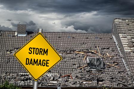 Foto de yellow damage warning sign in front of roof of house damaged by heavy hurricane tornado storm - Imagen libre de derechos