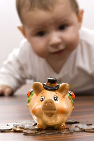 Young baby boy playing with piggy bank isolated