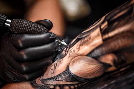 Foto de A professional tattoo artist introduces black ink into the skin using a needle from a tattoo machine.  - Imagen libre de derechos