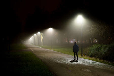 Foto de Single Person Walking on Street in the Dark Night - Imagen libre de derechos