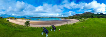 Foto de Golf Course With Carts And Clubs At The White Sand Beach Of Gairloch In Scotland - Imagen libre de derechos