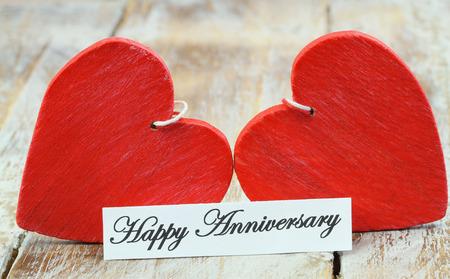 Foto de Happy Anniversary card with two red wooden hearts - Imagen libre de derechos