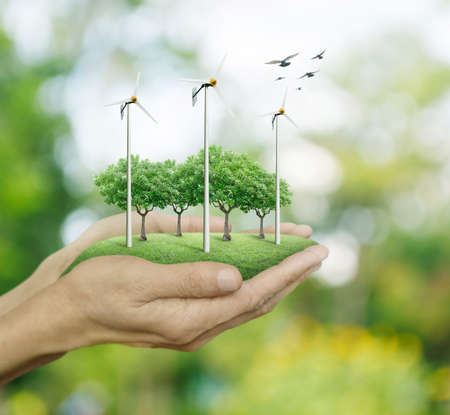 Photo pour Wind turbines and trees on hands over green bokeh background, Ecological concept - image libre de droit