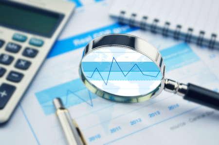 Foto de Magnifying glass, calculator and pen on financial graph, growth concept - Imagen libre de derechos