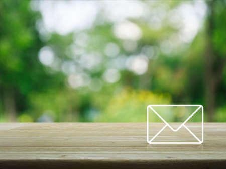 Photo pour Mail icon on wooden table over blur green tree in garden, Contact us concept - image libre de droit